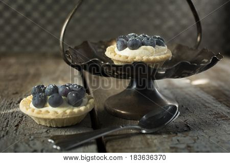Blueberry tarts with spoons in a stand with a rustic style