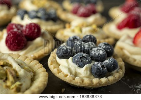 Blueberry, strawberry and pistachios tartlets on a wooden table