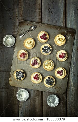 Top view of blueberry, strawberry and pistachios tartlets and aluminum plate on biscuit sheet on a wooden table