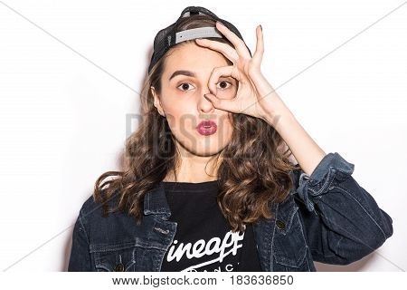 Pretty Cool Woman With Okay Sign On Eyes, Cap Having Fun Over White Background
