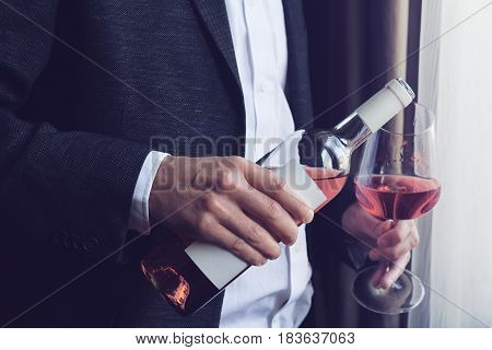 Horizontal close up of Caucasian man in black suit and white shirt pouring rose wine into a tall glass from a bottle in a bar by the window natural lighting