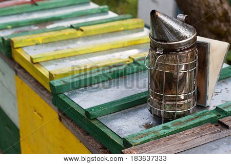metallic bee smoker equipment on top of beehives boxes