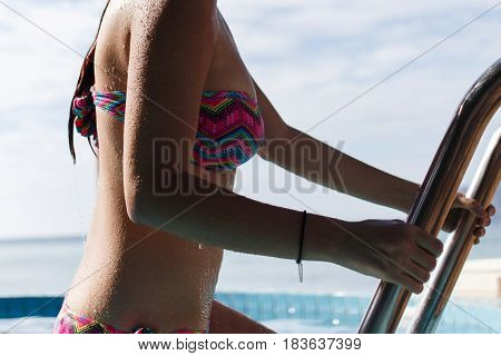Slender girl on ladder of pool in summer