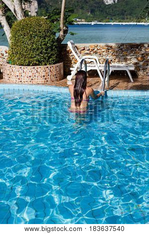 Woman at stairs of outdoor pool during day