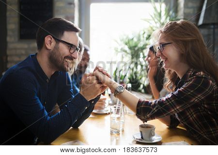 Happy beautiful couple flirting and dating in restaurant