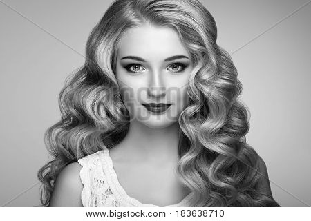 Beautiful girl with long wavy and shiny hair . Blonde woman with curly hairstyle. Perfect make-up. Fashion photo. Black and White photo