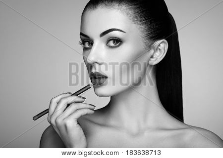 Beautiful woman paints lips with lipstick. Beautiful woman face. Makeup detail. Beauty girl with perfect skin. Red lips and nails manicure. Black and White photo