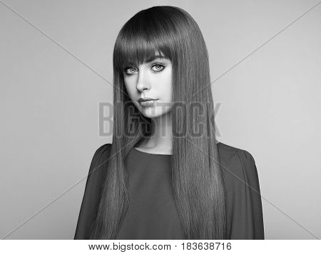 Portrait of beautiful woman with red hair. Colored long haircut. Perfect make-up. Girl in elegant violet dress. Red wig. Fashion photo. Black and White photo