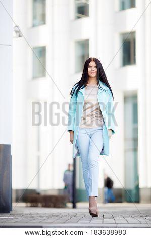 Beautiful girl walking down street on building background