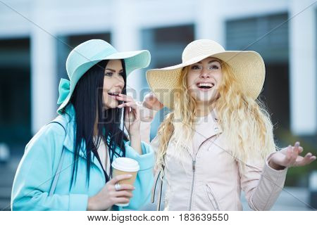 Two girls in hat with coffee on blurry background