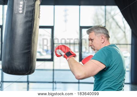 Senior Sportsman In Red Boxing Gloves Punching Bag In Fitness Class