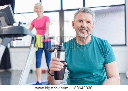 Senior Sportsman Sitting With Sport Bottle, Sportswoman On Treadmill Behind. Senior Fitness Class Co