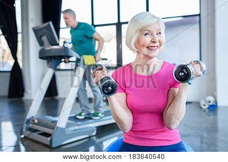 Senior Sportswoman Sitting On Fitness Ball With Dumbbells, Sportsman On Treadmill Behind In Senior F