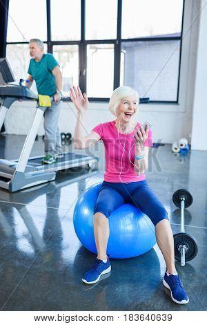 Senior Sportswoman Sitting On Fitness Ball With Smartphone, Sportsman On Treadmill Behind  In Senior
