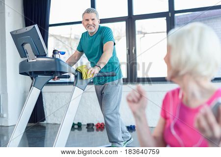 Senior Sportsman Training On Treadmill,  Senior Sportswoman On Foreground In Senior Fitness Class
