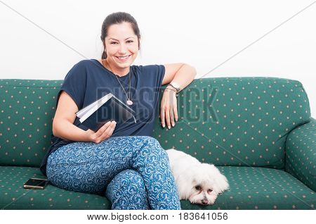 Relaxed Woman Reading Book While Sitting On Couch