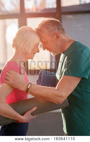 Happy Old Couple With Yoga Mats Touching Foreheads In Fitness Class