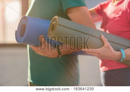 Close-up Partial View Of Fitness Couple Holding Yoga Mats In Gym