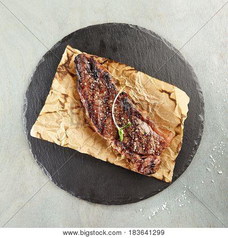 Restaurant Grilled Food - Delicious Grilled Striploin Steak. Gourmet Restaurant Steak Menu. Steak Served on Parchment with Green Herbs