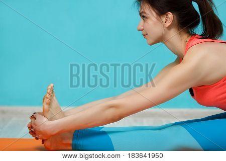 Brunette doing yoga exercises on rug in hall