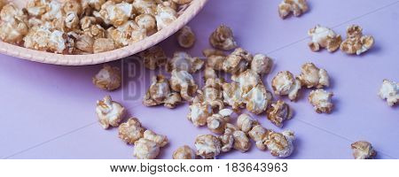 Sweet Popcorn In A Wicker Dish On A Purple Background,