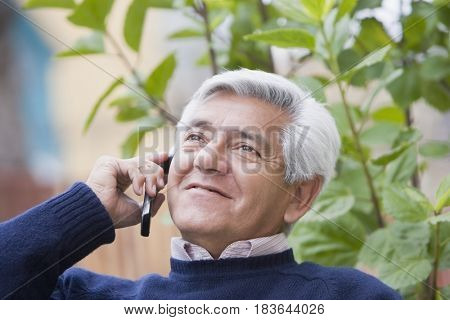 Senior Hispanic man talking on cell phone