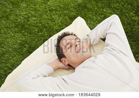 Hispanic man laying on grass