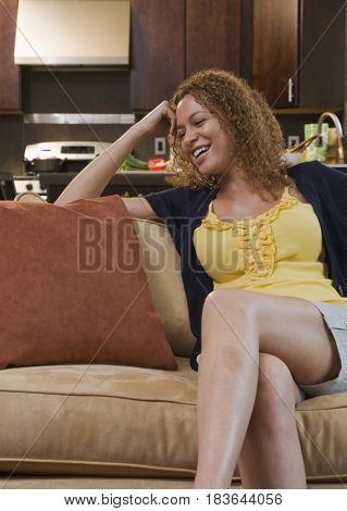 African woman relaxing on sofa