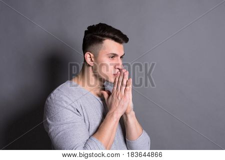 Hesitated. Facial expression and emotions. Thoughtful man praying, holding hands clasped near face on studio background