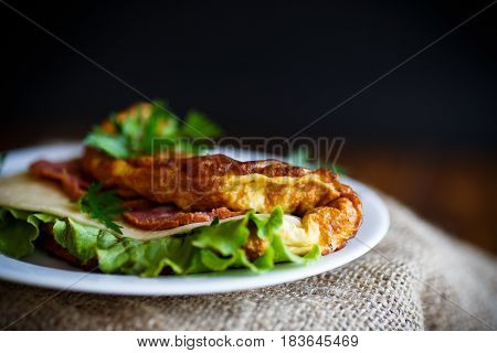 Hot stuffed omelette with cheese, sausage and salad leaves on a black background