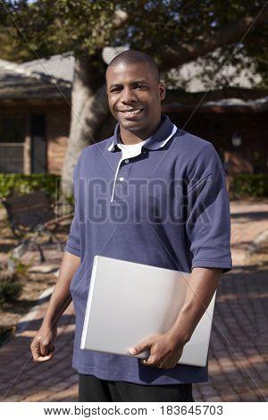 Black man carrying laptop