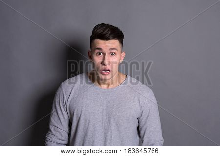 Surprised. Wonder man expressing amaze on face, standing on gray background, studio shot