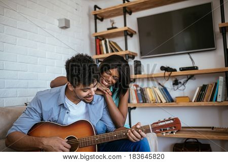 Photo of african american couple singing and playing guitar at home.