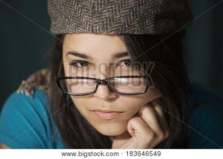 Serious Hispanic woman in cap and eyeglasses