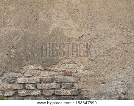 Old decaying brick wall. Background texture of peeled plaster at an old house. Old wall with crags.