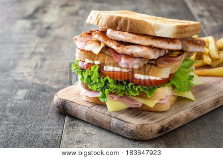 Traditional club sandwich with ham,cheese,bacon and chicken on wooden table