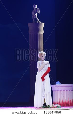 Blonde with a white face, in a white dress, depicts a statue