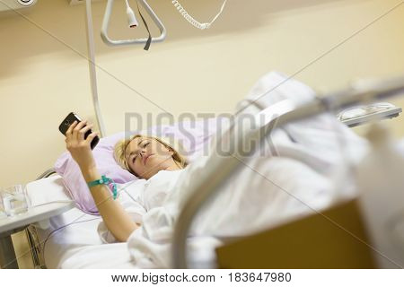 Bedridden female patient lying in hospital bed, using mobile phone while recovering after surgery.