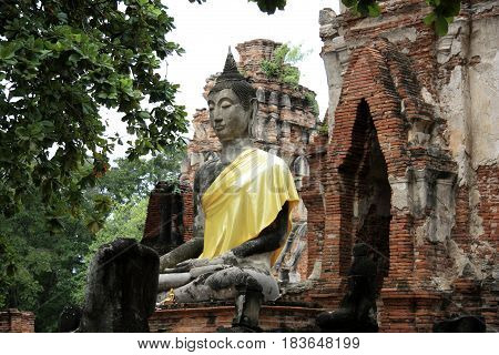 Ancient ruins of Chaiwattanaram temple in and sculpture of Buddha with yellow cloth in Ayutthaya in Thailand