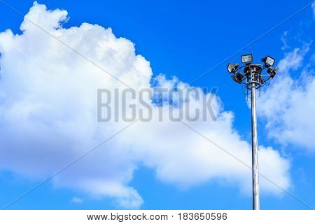 Spotlight and the sky clouds. Spotlights lighting tower at sport arena stadium.