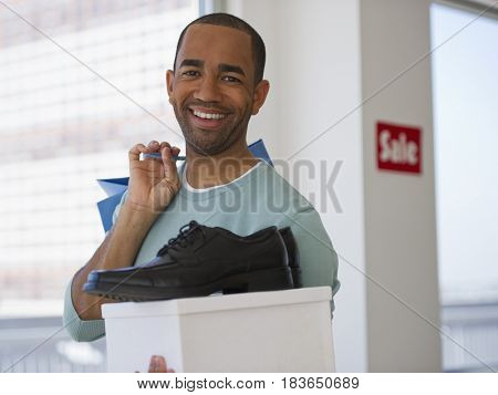 Mixed race shopper holding shoe and box