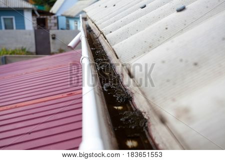 Dirty rain gutter on asbestos slate roof need to cleaning