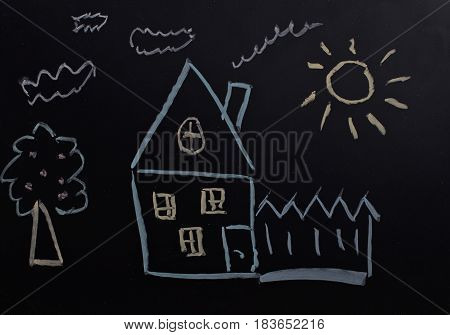 child's drawing with chalk on a blackboard house tree sun.