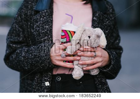 young stylish girl hands hold hot coffee and a small children's toy