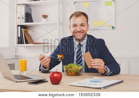 Man has healthy business lunch, vegetable salad, in modern office interior. Young handsome businessman in eyeglasses at working place, looking at camera. Diet and eating right concept.