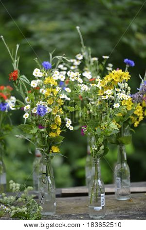 A collection of brightly coloured little summer bouquets put into glass bottles perched on top of a wooden table.