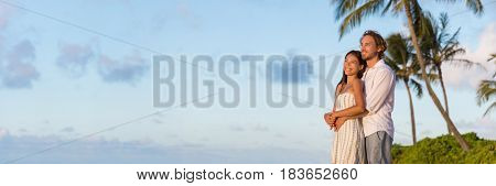 Relaxing couple watching sunset on beach vacation banner. multiracial people enjoying tropical holidays together hugging in love looking away at clouds sky copy space.