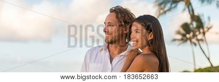 Relaxing multiracial couple watching sunset on beach vacation banner. Portrait of Asian woman, Caucasian man together enjoying looking at sky copy space.