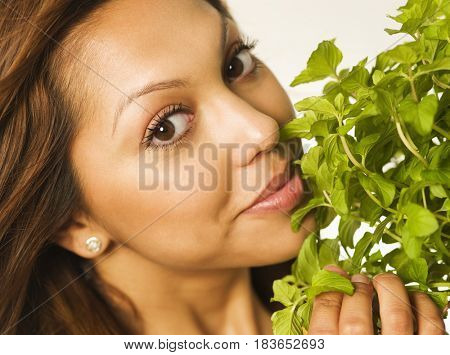 Close up of Hispanic woman smelling herbs