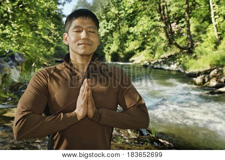 Mixed race man meditating near river